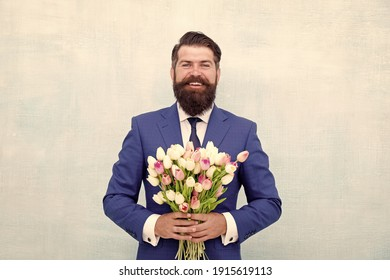 Womens day. March 8. Spring gift. Bearded man with flowers. Celebrate spring. Gentleman with tulips. Spring is coming. Romantic date. Let me invite you. Bearded man with tulip bouquet. Love date.