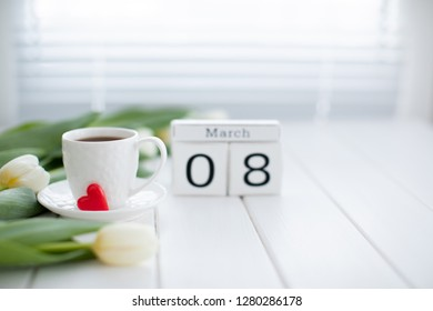 Women's day March 8 with wooden block calendar and fresh flowers. Calendar with the date of March 8 - Holiday  flowers. Background Spring Flowers Tulips and a cup of coffee on a white wooden Table.