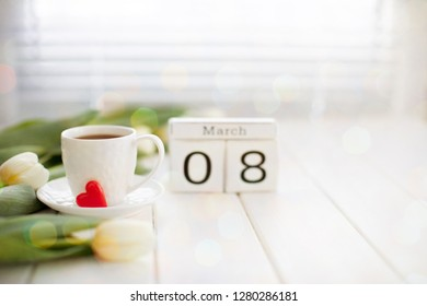 Women's day March 8 with wooden block calendar and fresh flowers. Calendar with the date of March 8 - Holiday  flowers. Background Spring Flowers Tulips and a cup of coffee on a white wooden Table .