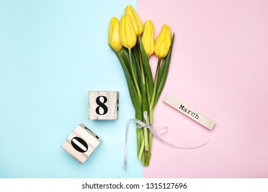 Women's Day on wooden calendar with yellow tulips on colorful background