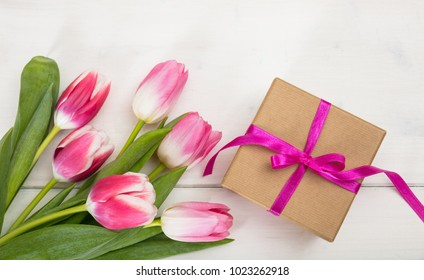 Women's day. Pink tulips bouquet and a gift on white wooden background, top view