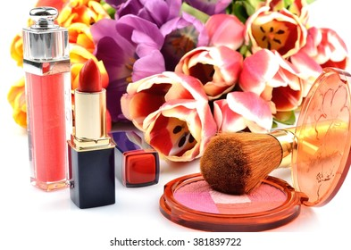Women's decorative cosmetics rouge, lipstick, flowers and tulips on a white background