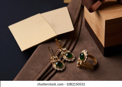 Women's diamond jewelry earrings and a ring with a green emerald stone and gift boxes with shopping bags. Empty cards with copy space for your text