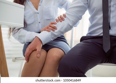 Womens discrimination. Nice unpleasant adult man sitting near his colleague and touching her legs while sexually harassing her