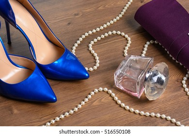 Women's fashion accessories, clothing, and footwear (scarf, jeans, perfume, shoes) on the wooden floor. Top view. Free space.