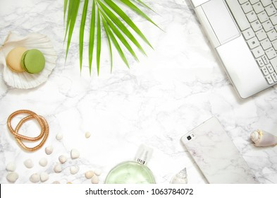 Women's fashion accessories, computer, phone, palm leaf on marble background.