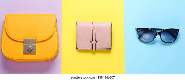 Women's fashion accessories on a pastel color background. Bag, wallet, sunglasses. Minimalistic fashion concept. Top view