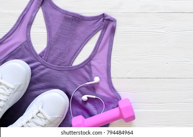 Womens fashion activewear clothing, shoes and accessories (ultra violet color top, white sneakers, dumbbells, headphones. View from above, Flat lay. Spring summer collection. flat lay