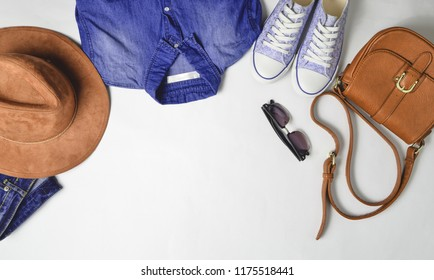 Women's fashion clothing and accessories. Jeans, denim shirt, sneakers, felt hat, leather bag, sunglasses, layout on a white background. Top view, flat lay,copy space