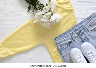 Womens fashion clothing shoes (white leather sneakers, blue jeans, yellow top (long sleeve t-shirt) and fresh flowers. Wish list or shopping overview, fashion concept. View from above, Flat lay. Trend
