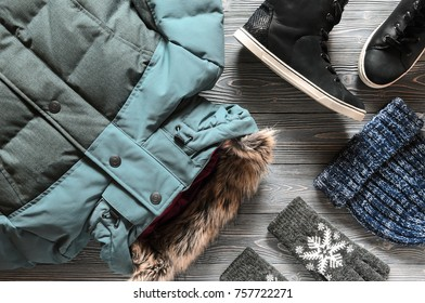 Women's fashion warm winter clothing and accessories - jacket, black leather high top sneakers, gloves and hat. Wish list or shopping overview concept. winter outfit. View from above. Flat lay