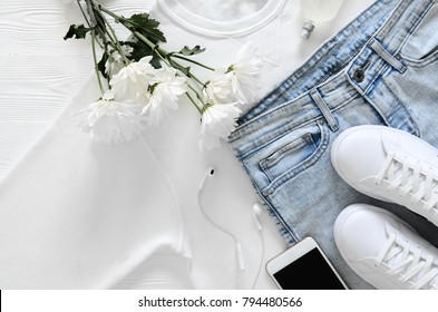 Womens fashion white clothing, shoes, accessories (white leather sneakers, blue jeans, sweatshirt, headphones, perfume, flowers. Fashion concept. View from above, Flat lay. Spring summer collection