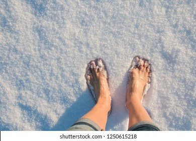 women's feet barefoot without shoes on frozen white fluffy snow