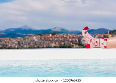 Women's feet in Christmas socks near the pool on the Kastoria town and neighborhood Orestias lake background. Greece