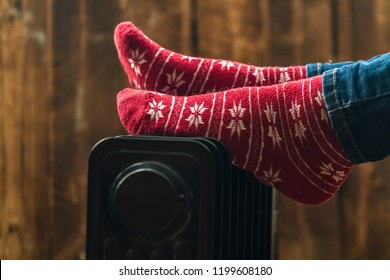 Women's feet in Christmas, warm, winter socks on the heater. Keep warm in the winter, cold evenings. Heating season