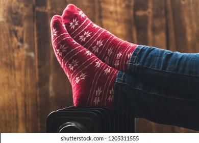 Women's feet in Christmas, warm, winter socks on the heater. Keep warm in the winter, cold evenings. Heating season