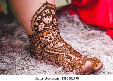 Women's feet on a white carpet with freshly applied tattoo on the feet.