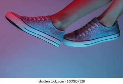 Women's feet with sneakers. Creative pop art pink blue neon color. Trendy gradient illumination. Night light