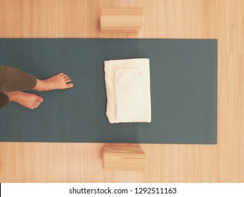 Women's feet standing on a dark green yoga mat made from rubber or pvc. There are towels, handkerchiefs and hard foam blocks as an accessory In yoga class all at wooden floor.