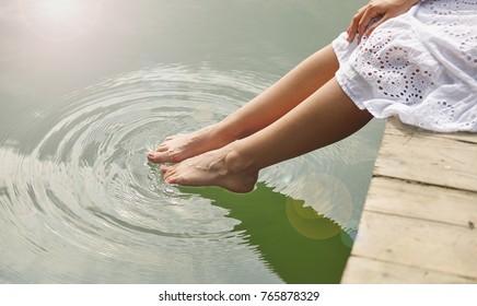 Women's feet in the water plunges feeling freshness