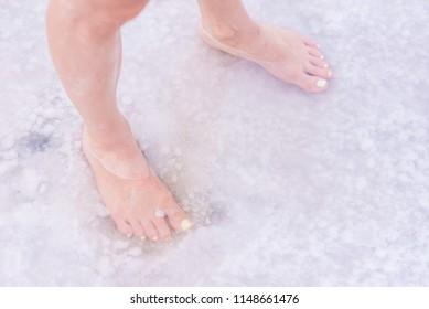 Women's feet with yellow nail Polish in salt water. Female legs in pink lake Bursol', Altai Krai. a woman standing in salt water barefoot.