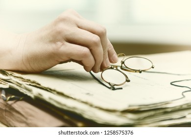 982544e5d34 women s fingers put a rimless eyeglasses on a pile of archival documents