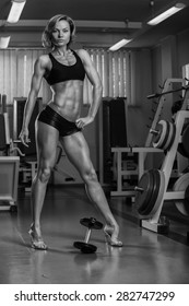 Women's fitness, the woman in the gym. Muscular blonde sports. The concept of women's bodybuilding.