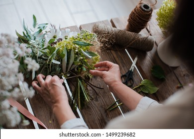 Women's girl strikes up a professional florist bouquet. Flower shop. Concept inspiration, floristry, greetings, spring, ornament flowers. close-up, top view