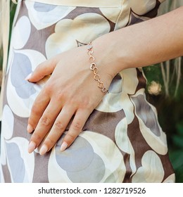 women's gold bracelet on the girl's hand, women's accessories, jewelry, gold bracelet with stones, women's jewelry, a girl with a bracelet on her arm, a bracelet with stones
