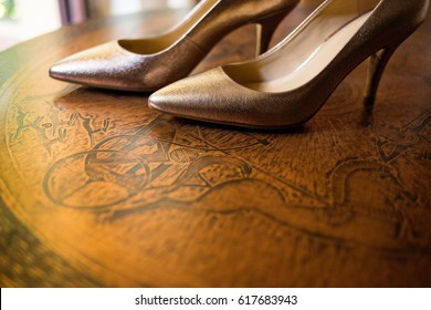 Women's gold leather high heels, Bridal shoes, Expensive stilettos on top of a brown vintage table