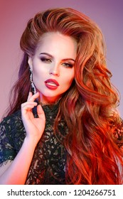 Women's hair. A luxurious young model with shiny, healthy, long red curls. Wavy hairstyle