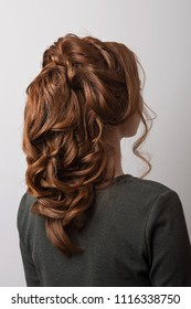 Women's hairstyle Eastern tail on the head of a girl with red hair back view close-up on a gray background.