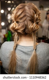 women's hairstyle. female hairstyle weaving. the girl in the beauty salon makes a hairdo. blonde with a beautiful hairdo