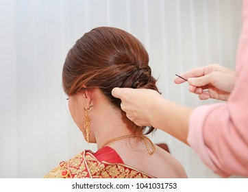 Women's hairstyle halo braid on the hair of the brown. Rear view.
