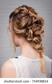 Women's hairstyle halo braid on the hair of the brown-haired rear view of the head turning left on a light background