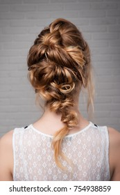 Women's hairstyle halo braid on the hair of the brown rear view on a light background