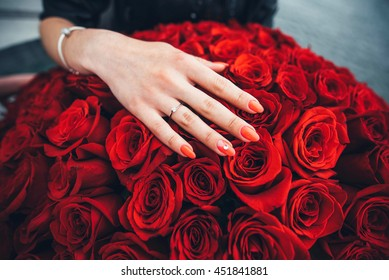 Women's hand with diamond ring on the red roses
