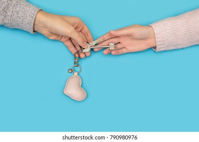 Women's hand goes to the man's hand on blue background. Men's hands give the keys on a blue background. Female hands take the keys that the man gives.