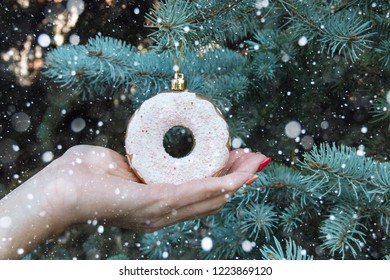 women's hand holding a Christmas toy donut on the Christmas tree background