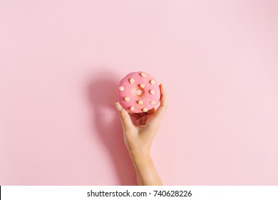 Women's hand holding donut on pink background. Minimal flat lay.