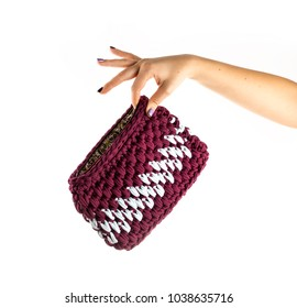 Women's hand is holding handmade crocheted and zipped clutch isolated on white background. Close up.