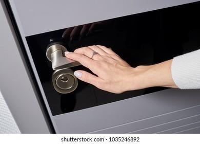 Women's hand opens modern gray-blue door