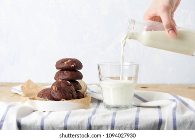 Women's hand pouring whole milk into a glass.Chocolate chip cookies with dulce de leche on a wooden table. Breakfast concept. Minimalism style