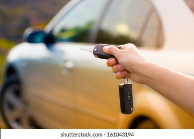 women's hand presses on the remote control car alarm systems