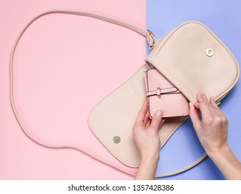 Women's hand put in bag leather wallet on pastel background. Top view, flat lay, minimalism