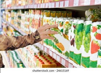 Womens hand selects the juice at the store
