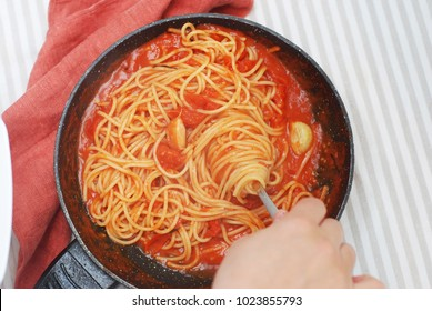 Women's Hand Taking Pasta Spaghetti with Fork from Pan. Spaghetti with Tomatoe Sauce. Top view. Homemade Food concept.