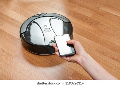 womens hand using mobile to control black robotic vacuum cleaner. modern smart cleaning technology. easier, safer and smarter way to work.