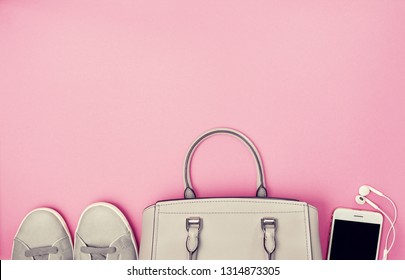 women's handbag, gray sneakers, a smartphone with headphones on a pink background. view from above. copy space. toning