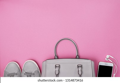 women's handbag, gray sneakers, a smartphone with headphones on a pink background. view from above. copy space